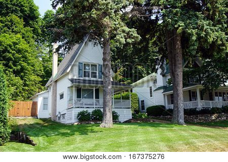 A Victorian home with a wraparound porch and a very steep roof, under the bluff on Fourth Street in Harbor Springs, Michigan, during August.