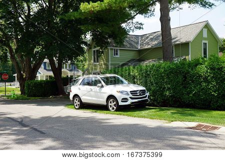 HARBOR SPRINGS, MICHIGAN / UNITED STATES -AUGUST 4, 2016: A white Mercedes-Benz sports utility vehicle is parked beside a hedge outside of a green home in Harbor Springs.