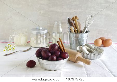 ingredients and bakeware for fresh homemade plum cake - still life