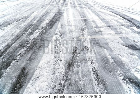 messy tire tracks in the street after snow