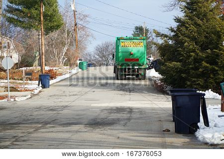 trash collection truck collecting garbage in residential street