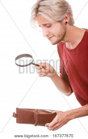 Broke young man holding magnifying glass looking for banknotes in empty wallet purse. Lack of money. Crisis and weak economy concept isolated on white