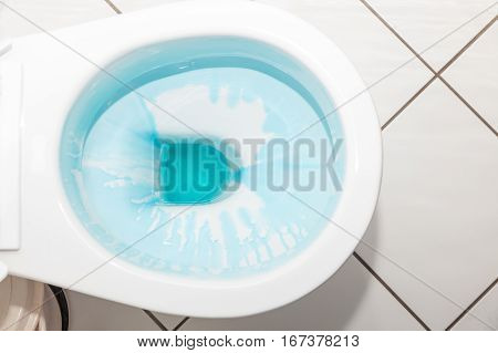 Cleaning and disinfection concept. White toilet bowl with blue detergent after flush.