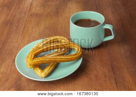 Churros, traditional Spanish, especially Madrid, dessert, often for Sunday breakfast, in the form of horseshoe, with a cup of chocolate on a wooden board texture, retro style, with copyspace