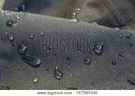 detail of fabric water repellent close up on an outdoor jacket material with water drops