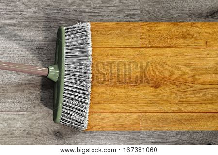 sweeping away the dust on wooden floor with a broom