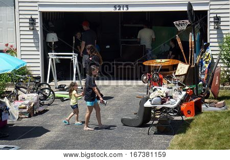 JOLIET, ILLINOIS / UNITED STATES - JUNE 17, 2016: People shop at a garage sale in the Wesmere Estates neighborhood of the Wesmere Country Club in Joliet.