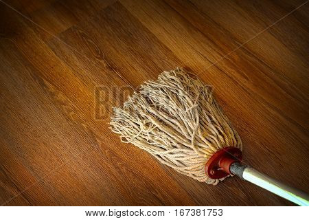 washing the wood floor with an old used mop