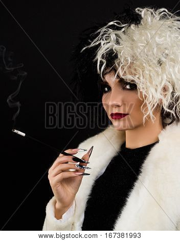 woman dressed up as halloween character Black and white colors . She has cigarette holder in her hand.
