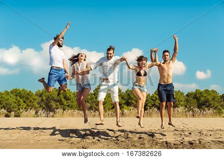 Group of friends together on the beach having fun. Happy young people jumping on the beach. Group of friends enjoying summer vacation on a beach.