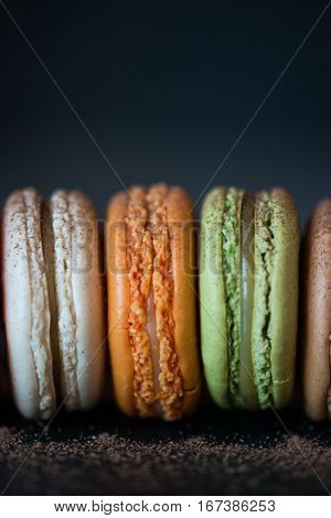 Close-up of colorful macaroons. Stack of sweet macaroons, green, white and orange color