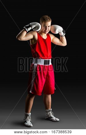 Young handsome boxer sportsman in red boxer suit and white gloves standing on black backgound. Copy space.