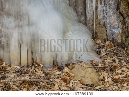 Large ice flow on the side of a hill with leaves and twigs on the ground