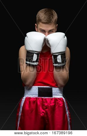 Young handsome boxer sportsman in red boxer suit and white gloves standing on black backgound. Protection stand. Copy space.
