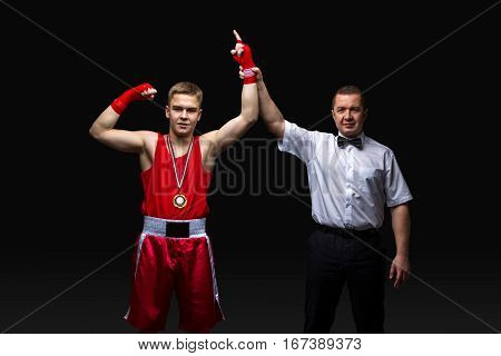 Boxing referee gives medal to young teen boxer in red form and white gloves. Winner. Studio shot on black background. Copy space.
