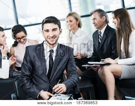 Portrait of a young successful manager - director of a close-up on a background of working business team in a modern office