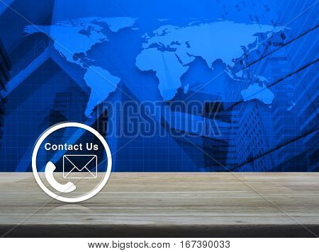 Telephone and mail icon button on wooden table over world map and city tower background Contact us concept Elements of this image furnished by NASA