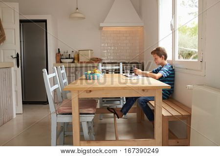 Boy Uses Mobile Phone Whilst Doing Homework At Kitchen Table