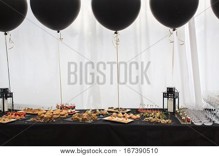 Different snacks on the black table and black balloons behind. Candle lights and stemware