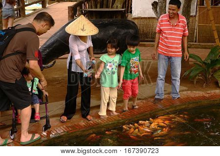 Mekong river island, Vietnam, December 27, 2016: Unidentified vietnamese tourisit with kids feed gold fish in pool in tropical park in island on Mekong river delta in Vietnam, December 27, 2016.