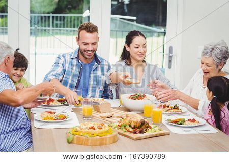 Smiling multi generation family having food at dining table in home