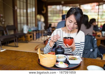 Woman eating in Japanese restaurant