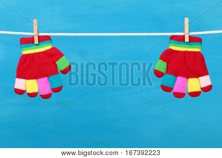 Striped colorful gloves hanging on the clothesline on blue wooden background
