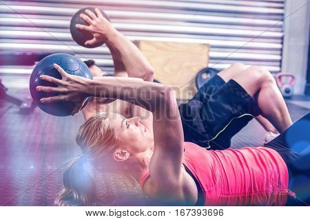 Fit couple doing abdominal ball exercise at gym