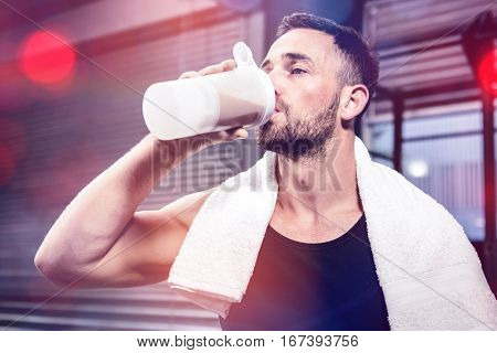 Muscular man drinking protein shake at crossfit gym