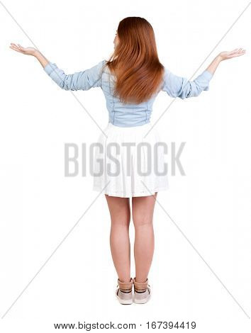 Back view of Beautiful woman in dress looking at wall and Holds  hand up.  young redhead girl standing. Rear view people. Isolated over white background.