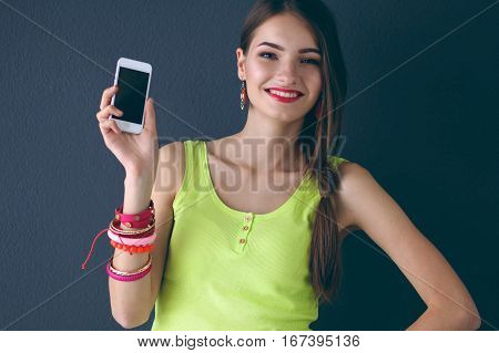 Beautiful young woman holding cellphone, standing near dark wall.