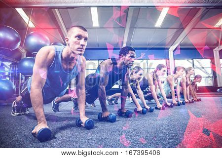 Fitness class in plank position with dumbbells at gym