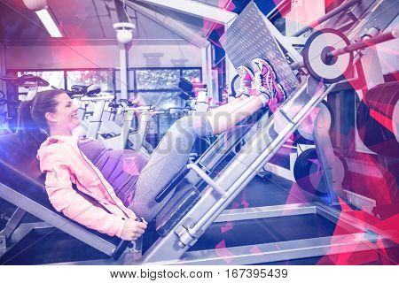 Pregnant woman using weight machine at gym