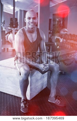 Portrait of male athlete sitting on wooden box in fitness studio