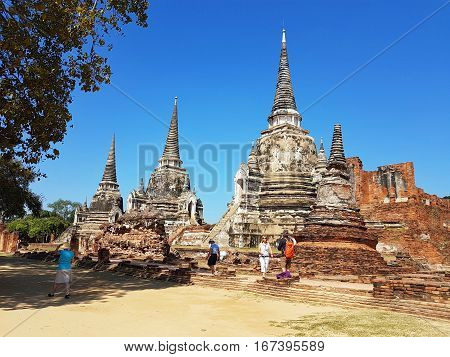AYUTTHAYA THAILAND - NOVEMBER 29: Unidentified tourists visit Wat Phra Sri Sanphet in the Ayutthaya Historical Park on November 29 2016 in Ayutthaya Thailand