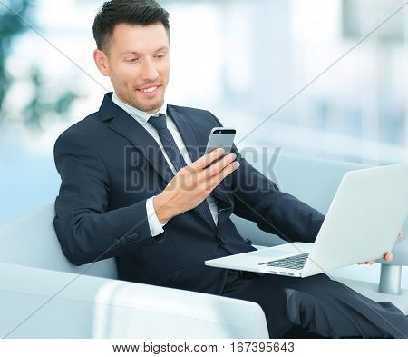 closeup of a businessman sitting in a chair with your smartphone and working on laptop in the lobby of the Bank.the photo has a empty space for your text