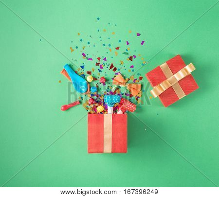 Red gift box with various party confetti balloons streamers noisemakers and decoration on a green background. Colorful celebration background. Flat lay.