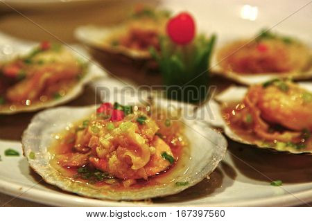 clams cooked on plate in restaurant with vegetables and sauce