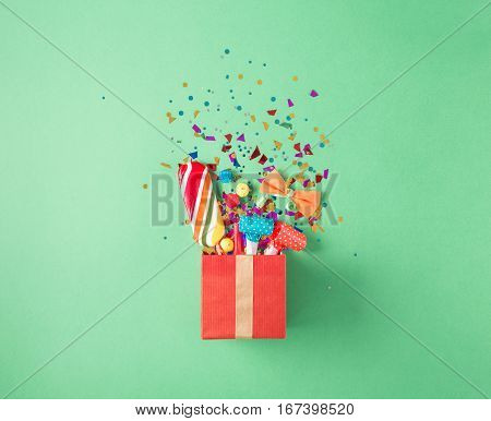 Red gift box with various party confetti balloons streamers noisemakers and decoration on a green background. Flat lay