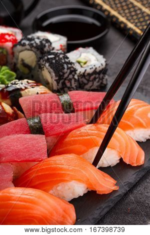 Japanese Cuisine. Sushi N Black Chopsticks On A Stone Plate And Black Concrete Background.