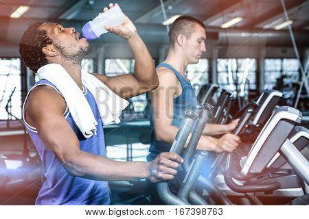 Man drinking water while using elliptical machine at gym