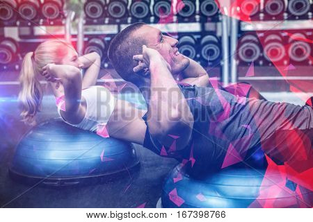 Fit couple doing sit ups on bosu ball at gym