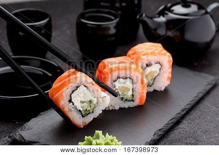 Salmon Sushi Roll On A Stone Plate With Chopsticks Over Concrete Background.