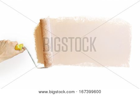 Hand holding a paint roller with a gray drawn strip of gray paint for advertising copy isolated on white background