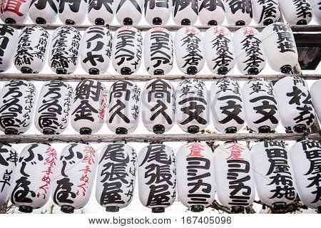 Japanese decorations with japanese inscriptions written inside a buddhist temple. The white colored round shaped designs looks beautifully arranged in a row.