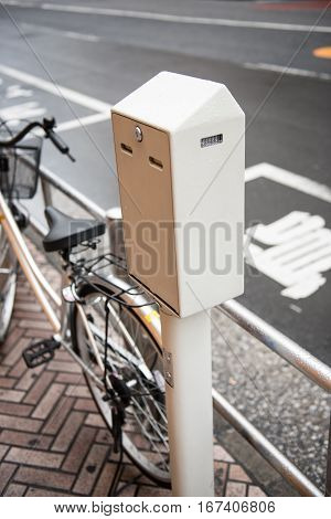 A bicycle is seen parked on a parking lot beside the road. A locker is also seen on the picture. One the background, the road is seen with white markings on it.