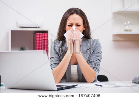 Young businesswoman is having allergy problem at work.