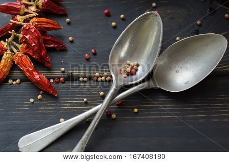 Two old tin spoons with red hot chili cayenne peppers dried variety - spicy ingredient on wooden table