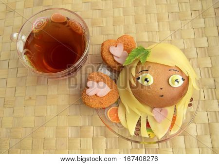 Sandwich in the form of the head of the girl and tea. Sandwich is made of a roll and cheese. Creative food for darlings and children.