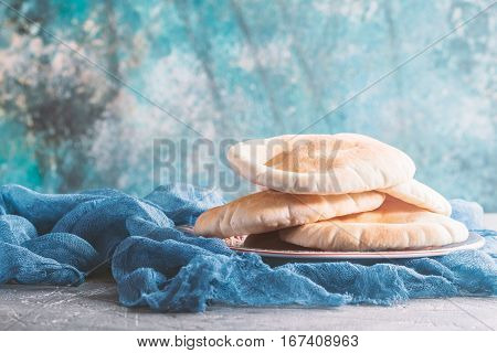 Pita or Arabic bread on gray table with blue background